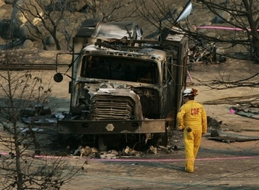 A firefighter from the California Department of Forestry examines the burned-out crew transport rig where four firefighters died and one was seriously burned fighting the Esperanza fire in Twin Pines, Calif., Friday, Oct. 27, 2006.