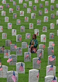 A Girl Scout places flags at Los Angeles National Cemetary - AP Photo